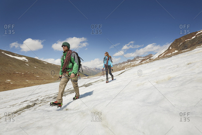 Young couple hiking down ice on Val Senales Glacier, Val Senales, South Tyrol, Italy