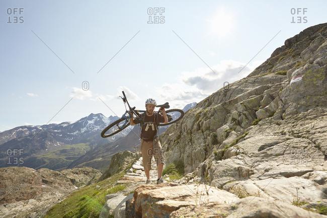 Young man carrying  mountain bike up path at Val Senales Glacier, Val Senales, South Tyrol, Italy