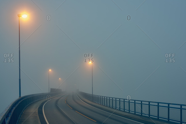 Diminishing perspective of misty road illuminated by street lights, Haugesund, Rogaland County, Norway