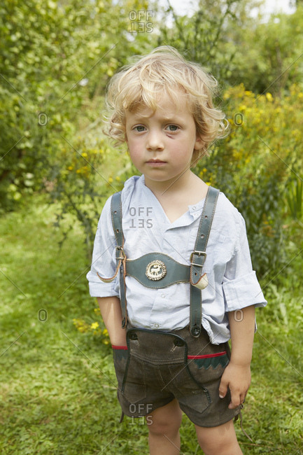 Portrait of sad boy with scratched face wearing lederhosen