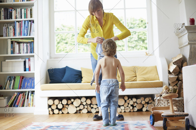 Mother helping son to get dressed