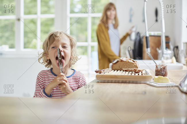 Mother and son in kitchen, son licking knife with chocolate on it