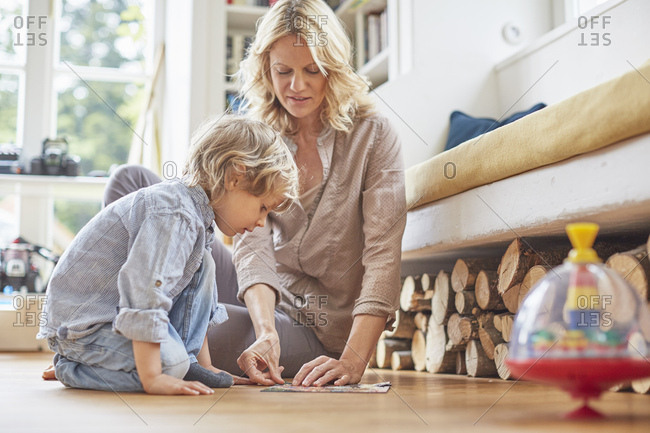 Mother and son sitting on floor, doing puzzle together