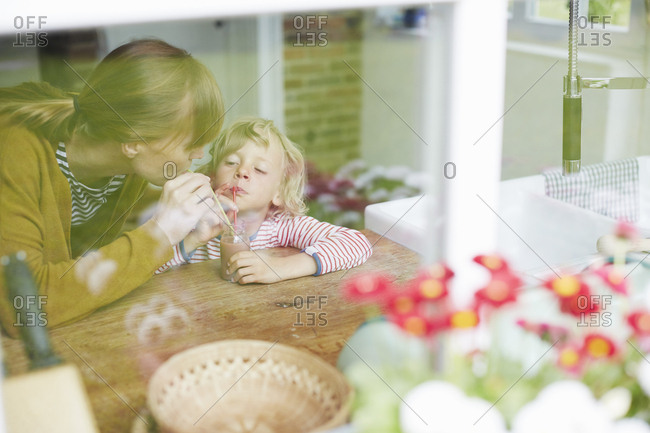Mother and son sharing a drink together, view through window