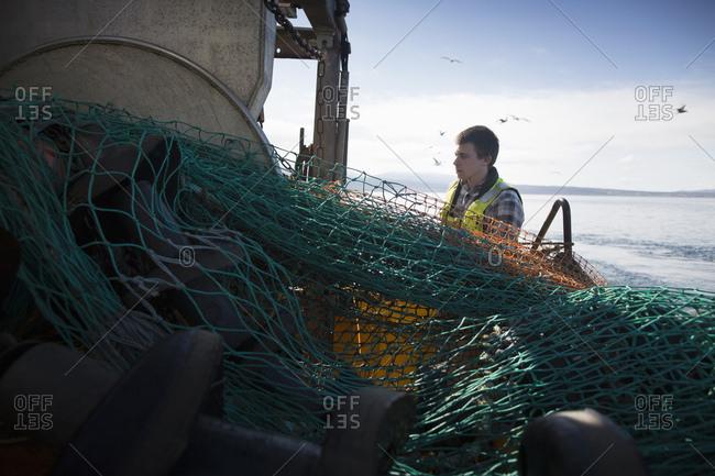 Fisherman preparing net, Isle of Skye, Scotland