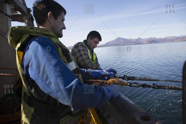 Fisherman releasing net into sea, Isle of Skye, Scotland