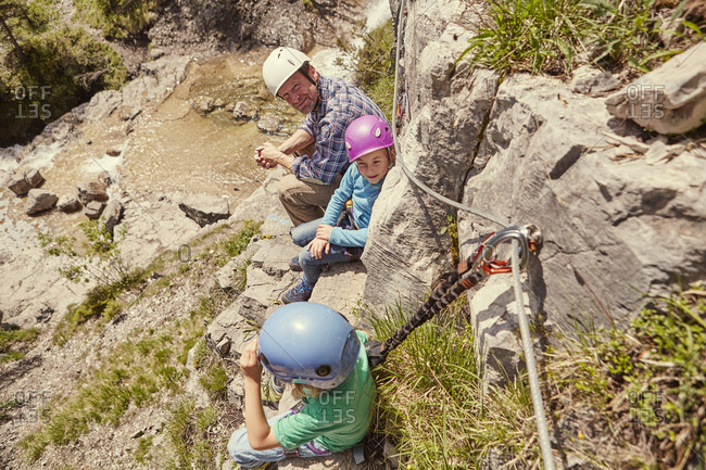 Father and children enjoying view on rocks, Ehrwald, Tyrol, Austria