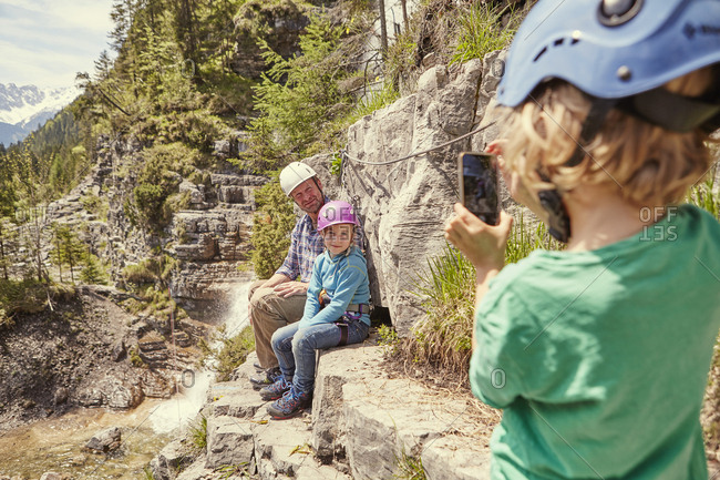 Father and children taking photograph on hill, Ehrwald, Tyrol, Austria