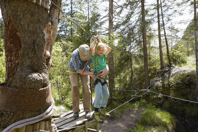 Father and child preparing for high rope in forest, Ehrwald, Tyrol, Austria
