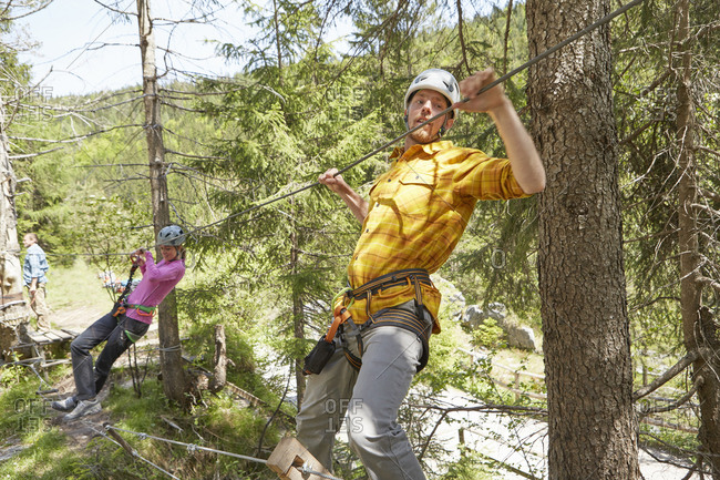 Climbers on rope in forest, Ehrwald, Tyrol, Austria