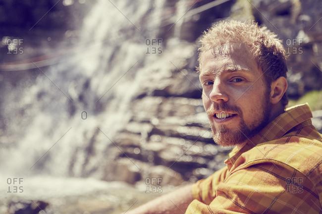 Man relaxing by waterfall, Ehrwald, Tyrol, Austria