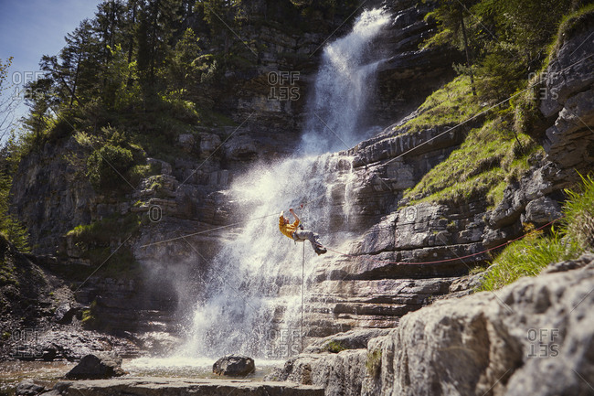 Man rappelling waterfall, Ehrwald, Tyrol, Austria