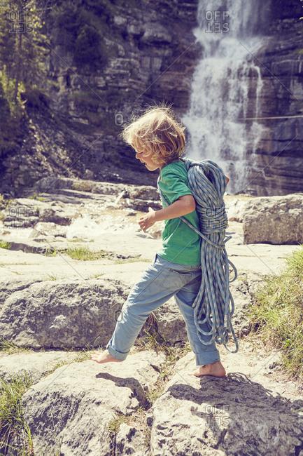 Boy carrying rope by waterfall, Ehrwald, Tyrol, Austria