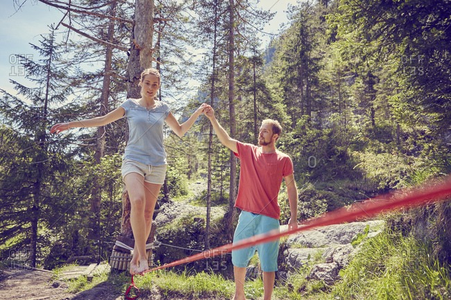 Woman balancing on rope with help from man, Ehrwald, Tyrol, Austria