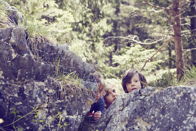 Three children hiding behind rocks in forest