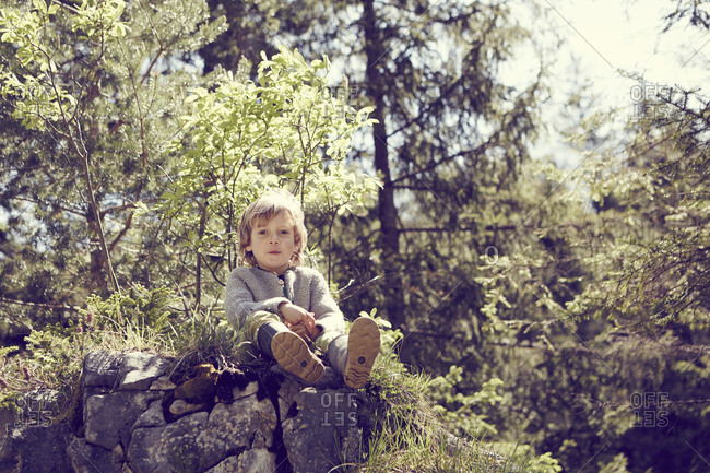 Young boy relaxing on rocks in forest
