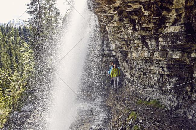 Young couple walking underneath waterfall, Tyrol, Austria