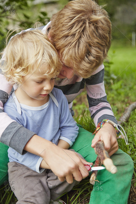 Boy sitting with younger brother using a penknife on twig in garden