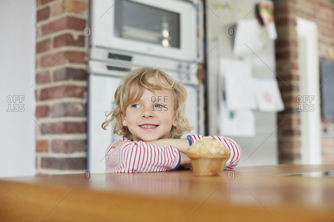 Young boy standing by kitchen counter,with muffin on counter in front of him