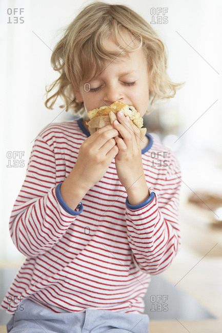 Young boy eating muffin - Offset