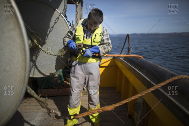 Fisherman reeling in net, Isle of Skye, Scotland