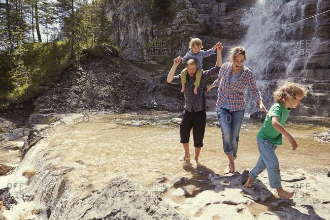 Two generation family having fun by waterfall, Ehrwald, Tyrol, Austria