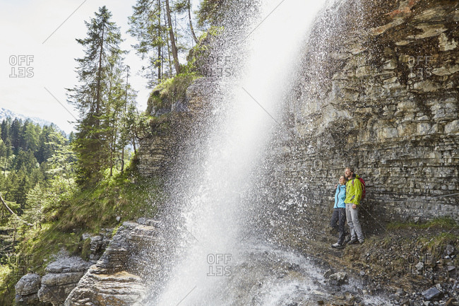Young couple standing underneath waterfall, looking out,  Tyrol, Austria