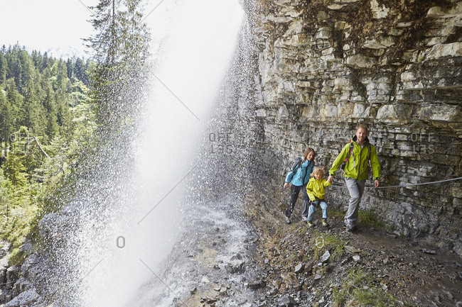 Young family, walking underneath waterfall