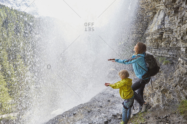 Mother and son, standing underneath waterfall, hands out to feel the water, rear view
