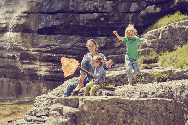 Mother and sons, sitting on rocks by waterfall, fishing with net