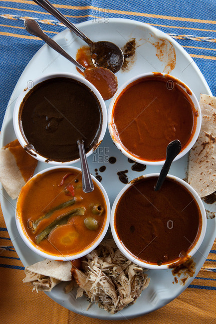 Variety of mole sauces in bowls on a plate with shredded meat