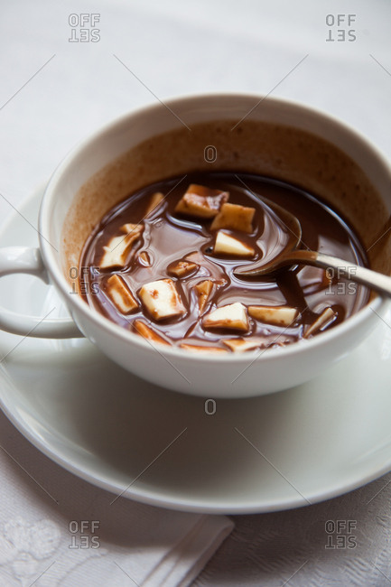Mug of hot chocolate with pieces of cheese