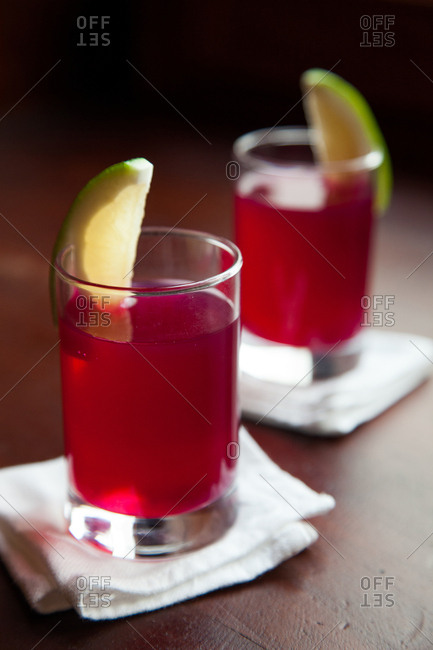 Red cocktails in glasses garnished with a wedge of lime