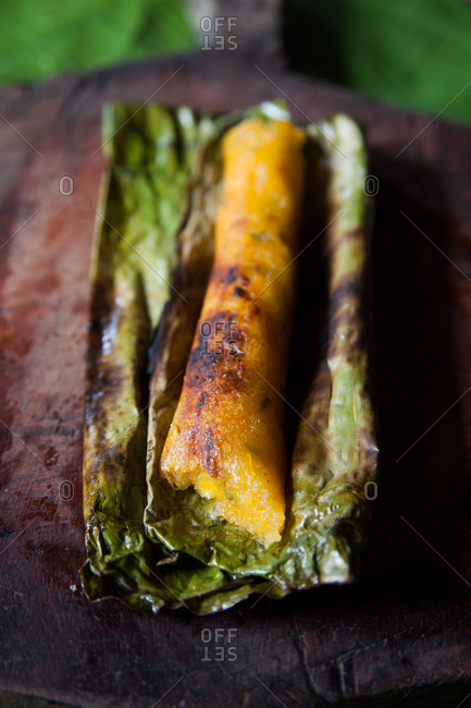 Grilled whole plantain wrapped in a green leaf