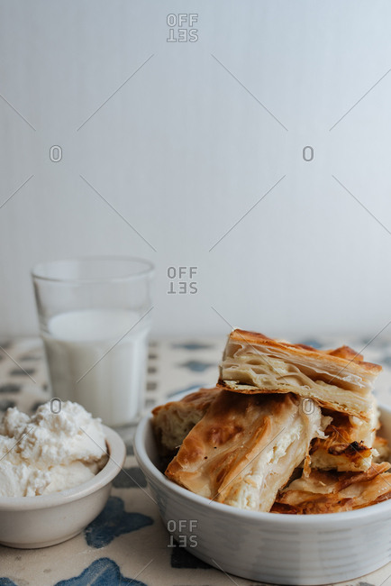 Slices of homemade cheese pie, glass of milk and cheese