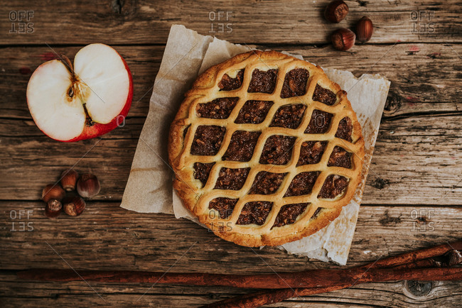 Apple and hazelnut pie, surrounded by apple, hazelnuts, and cinnamon