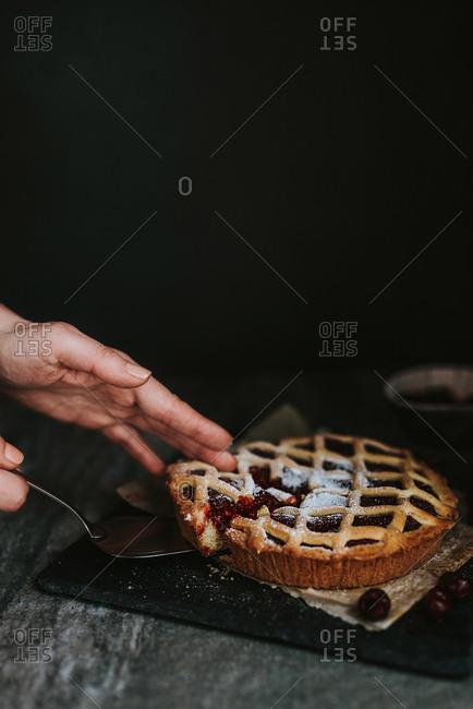 Hands taking one slice of cherry pie
