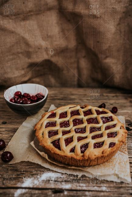 Sweet cherry pie placed next to frozen cherries