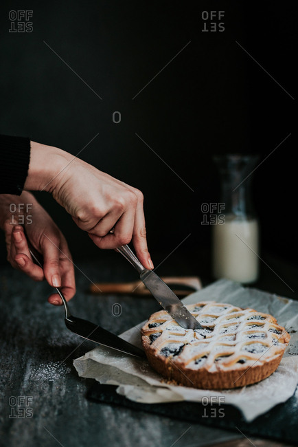 Hands cutting a slice of poppy seed pie, next to bottle of milk