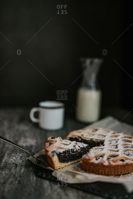 Cut slice of poppy seed pie next to milk