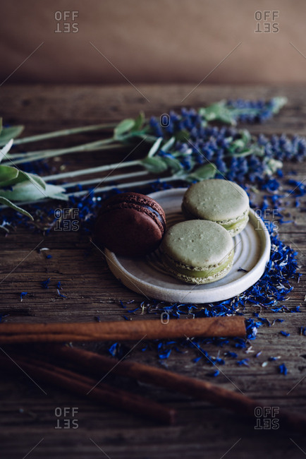 One chocolate and two pistachio macaroon on the wooden background