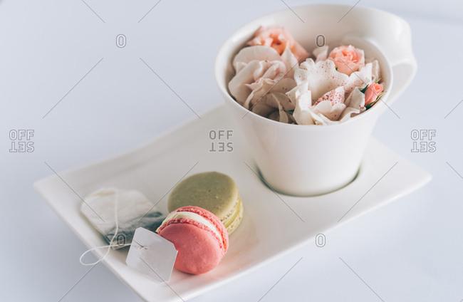 A cup of tea filled with rose petals, next to macaroons and tea bag