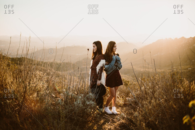 Two women with brown hair posing back to back in golden light on a hillside wearing stylish clothing.