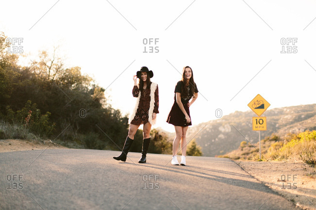 Fashionable young models posing and laughing in the middle of a road in the hills