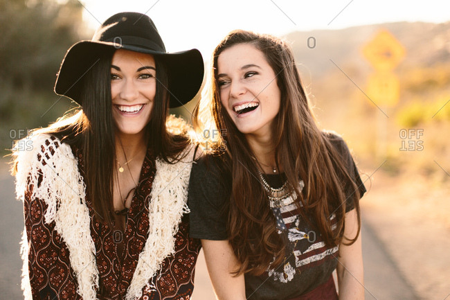 Best friends laughing and smiling at each other wearing a hat and accessories