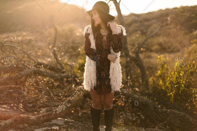 Fashion portrait of young woman posing in nature wearing short dress, hat, and boots