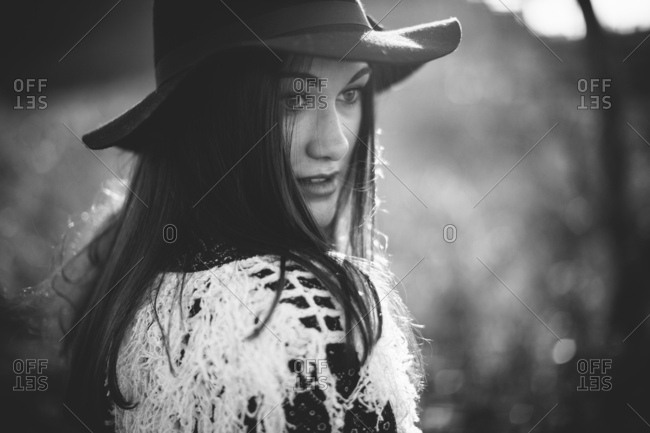Black and white portrait of woman with dark hair looking over shoulder wearing fashionable hat