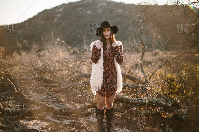 Stylish woman posing in nature wearing dress with sleeves, hat, and boots