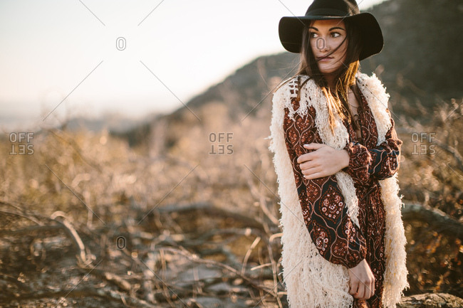 Stylish woman posing in nature wearing dress with sleeves and a hat