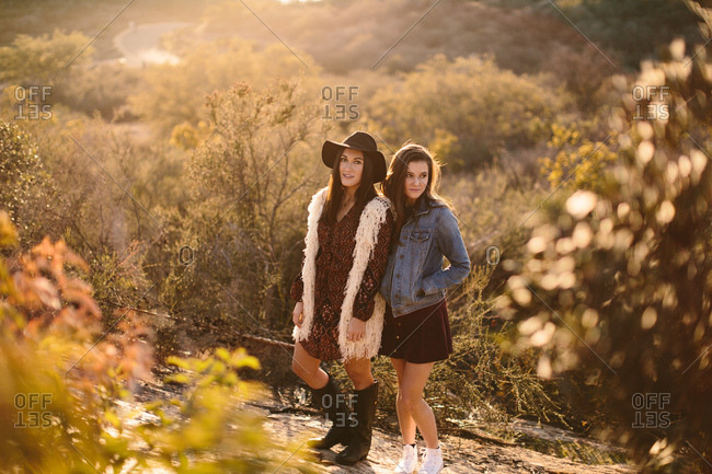 Stylish girlfriends posing in nature at golden hour wearing jean jacket, skirt, and hat